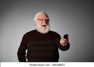 Portrait of senior man reading text message on his smart phone looking excited against grey background