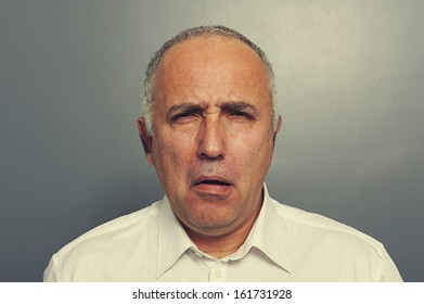 portrait of senior man with silly expression on his face over grey background