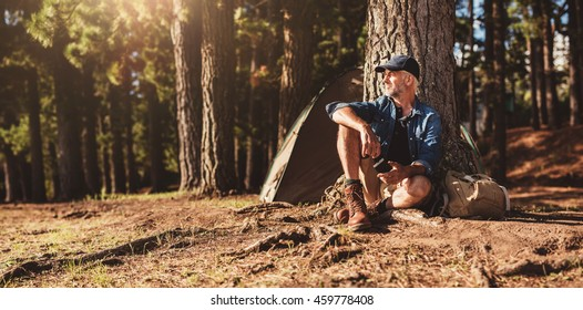 Portrait of senior man sitting by a tree with a tent in background. Mature man sitting at a campsite.