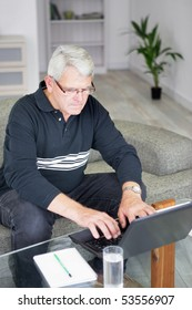 Portrait of a senior man sitting in front of a laptop computer