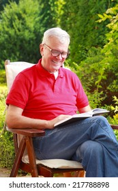 Portrait of senior man sitting at garden and reading funny stories in book.