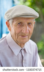 portrait of  senior man sitting near his house in the village