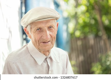 portrait of  senior man sitting near his house in the village