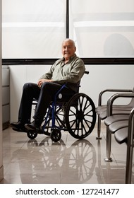 Portrait of senior man sitting on wheelchair in hospital lobby