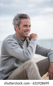 Portrait of a senior man sitting on a rock at the beach. He wears a sweater