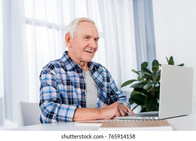 portrait of senior man sitting at table and using laptop at home