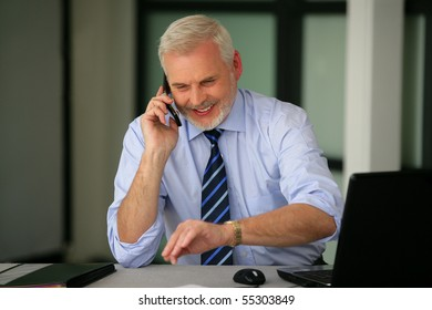 Portrait of a senior man smiling in suit with a phone and a laptop computer