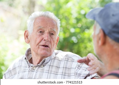Portrait of senior man smiling and talking to his friend in park