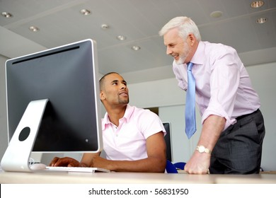 Portrait of a senior man smiling and a young man sitting in front of a desktop computer