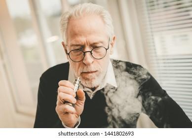 Portrait of senior man smoking electronic cigarette