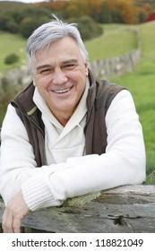 Portrait of senior man standing in field