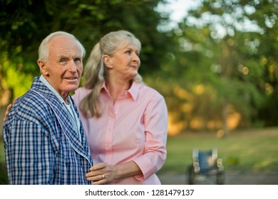 Portrait of a senior man standing with his wife in a garden.