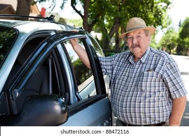 Portrait of senior man standing near car