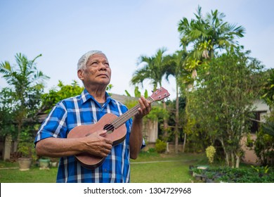 Portrait of senior man standing playing ukulele and looking up to sky in his garden. Relaxing by singing and play guitar for good mental health. People and health care concept
