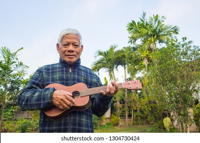Portrait of senior man standing playing ukulele and looking at the camera in his garden. Relaxing by singing and play guitar for good mental health. People and health care concept