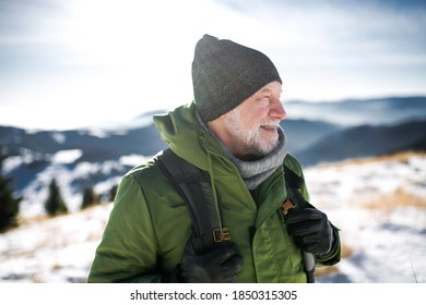 Portrait of senior man standing in snow-covered winter nature.