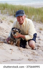 Portrait Of Senior Man Taking Dog For Walk On Beach