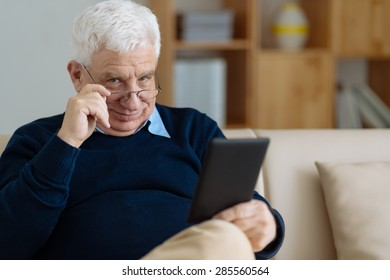 Portrait of senior man with touchpad at home