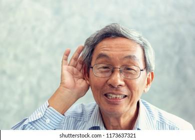 Portrait of senior man to trying hear something sound around him.