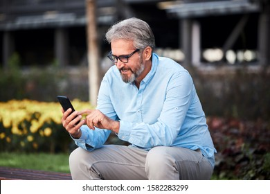 portrait of a senior man using a cell phone in the city