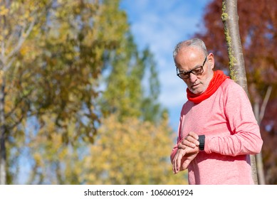 Portrait of a senior man using a smart watch.