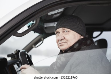 Portrait of senior man wearing knit cap, scarf, jacket sitting behind wheel of his car and looking through window - winter driving or mature drivers concept