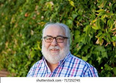 Portrait of senior man with white beard in the garden