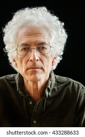 Portrait of a senior man with white curly hair against a black background.