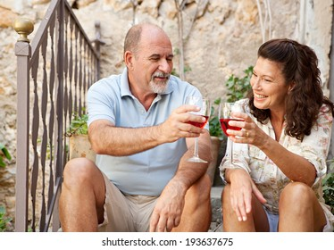 Portrait of a senior man and woman sitting on the stone steps of luxury hotel garden on holiday drinking wine and toasting in celebration, relaxing on vacation. Mature people, outdoors lifestyle.