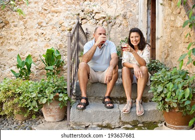 Portrait of a senior man and woman sitting on the stone steps of luxury hotel garden during a sunny day on holiday drinking wine together and relaxing on vacation. Mature people, outdoors lifestyle.