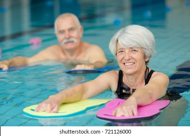 portrait of senior man and woman in swimming pool