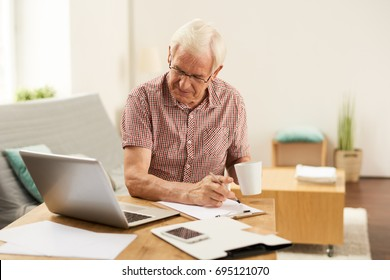 Portrait of senior man working with laptop at home counting finances and drinking coffee