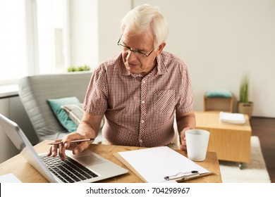 Portrait of senior man working with laptop at home counting finances and typing