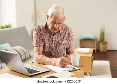 Portrait of senior man working with laptop at home counting finances