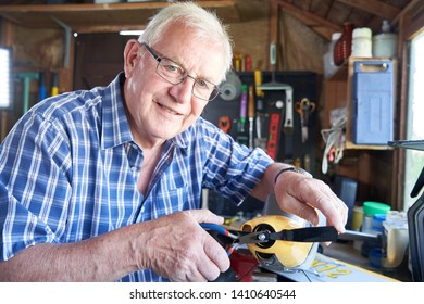 Portrait Of Senior Man Working On Model Radio Controlled Aeroplane In Shed At Home