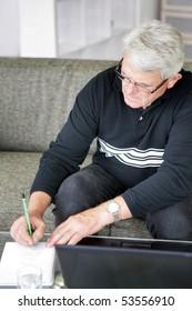Portrait of a senior man writing on a document