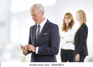 Portrait of senior managing director standing at office and using his mobile phone while businesswomen standing at background.