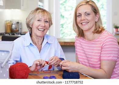 Portrait Of Senior And Mature Female Friends Knitting At Home Together