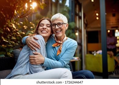portrait of a senior mother and adult daughter, hugging, smiling. Love, affection concept