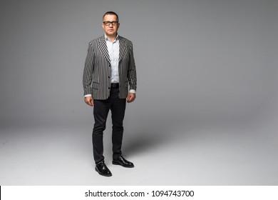 Portrait of a senior older business man standing wearing dark sunglasses on white background