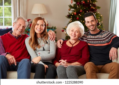 Portrait Of Senior Parents With Adult Offspring Wearing Festive Jumpers Sitting On Sofa In Lounge At Home On Christmas Day