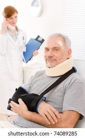 Portrait of senior patient with broken arm in doctor office