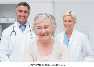 Portrait of senior patient smiling with doctors in clinic
