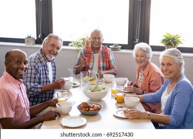Portrait of senior people having breakfast at table in nursing home