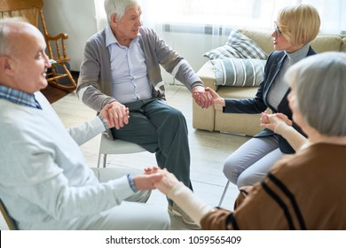 Portrait of senior people holding hands in group therapy session lead by female psychiatrist, copy space