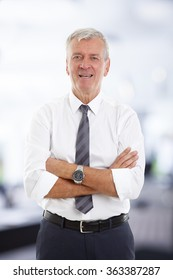 Portrait of senior professional man with arms crossed standing at office and looking at camera.