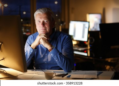 Portrait of senior professional man thinking about how to solve the problem while sitting at office in front of computer and working late.