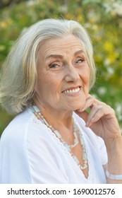 Portrait of senior smilling beautiful woman posing in spring park