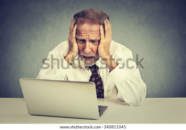 Portrait senior stressed man working on laptop sitting at table isolated on gray wall background
