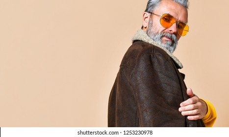Portrait of senior stylish rich man with a beard and mustache in a leather coat, standing half a turn his back and stern looking into the camera throught yellow modern glasses